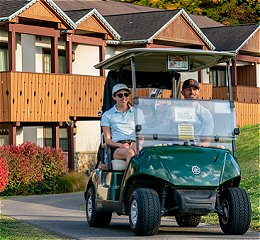 Two people in golf cart leaving the inn for a round of golf